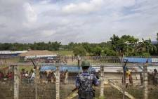 FILE: This file photo was taken on 24  August 2018 shows a Myanmar border guard police patrol watching over Rohingya refugees settlement in the 'no man's land' zone between Myanmar and Bangladesh border as seen from Maungdaw, Rakhine state during a government-organized visit for journalists. Picture: AFP.