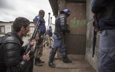 During a service delivery protest in Klipheuwel, Cape Town, Saps and Law Enforcement prepare to breach a house with suspects hiding inside. Picture: Thomas Holder/EWN