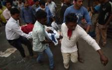 Indian local residents and rescue workers carry a survivor after a fire incident at the ESIC Kamgar hospital in Mumbai on December 17, 2018. Six people were dead after a fire broke out in a five-storey hospital, local media reported. Picture: AFP.