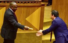 A screengrab of President Cyril Ramaphosa handing DA Chief Whip John Steenhuisen a cigar in Parliament. Picture: YouTube