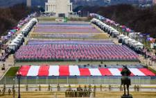 Members of the National Guard look on as American flags decorate the 'Field of Flags' at the National Mall ahead of the inauguration of US President-elect Joe Biden on the West Front of the US Capitol on 20 January 2021 in Washington, DC. Picture: Tasos Katopodis/POOL/AFP