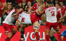 Reds player Jake Schatz (C) is tackled during the rugby union tour match between the Queensland Reds and the British and Irish Lions at Suncorp Stadium in Brisbane on 8 June 2013. Picture: AFP/Patrick Hamilton