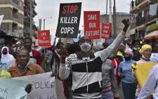A demonstrator gestures while holding a placard during a demonstration against what they term as arbitrary police killings in the Mathare slum in Nairobi on 8 June 2020. Picture: AFP