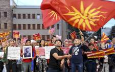 FILE: Demonstrators wave flags in front of the parliament building in Skopje on 23 June 2018 during a protest against the new name of the country, the Republic of North Macedonia. Picture: AFP