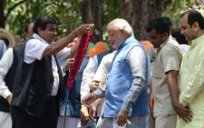 Chief Minister of the western Indian state of Gujarat and Bharatiya Janata Party (BJP) prime-ministerial candidate Narendra Modi (R) receives a garland from party leader Nitin Gadkari (L) after arriving at party headquarters in New Delhi on 17 May 2014. Picture: AFP/SAJJAD HUSSAIN