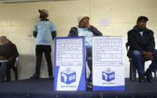 FILE: An IEC official sits behind two ballot boxes as she waits for voters. Picture: EWN