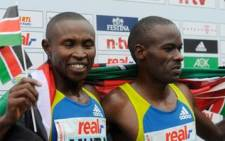 Kenya's Patrick Makau (R) and his compatriot Geoffrey Mutai celebrate after the Berlin marathon on September 26, 2010. Picture: AFP.