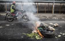 A man on a motorcycle drives past a burning tire and waste in the Nairobi slum of Mathare on 12 August 2017, where demonstrations continued overnight following the announcement that President Uhuru Kenyatta had won the presidential election. Picture: AFP.
