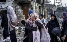 FILE: Palestinian women react amid the destruction in the northern district of Beit Hanun in the Gaza Strip during a humanitarian truce on 26 July, 2014. Picture: AFP.