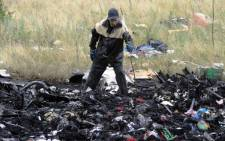A rescue worker uses sticks to mark the location where bodies of victims have been found at the site of the crash of a Malaysian airliner carrying 298 people from Amsterdam to Kuala Lumpur in Grabove, in rebel-held east Ukraine, on 18 July 2014.Picture:AFP.