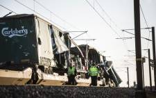 Two men walk past a damaged cargo train after an accident on 2 January 2019 in Nyborg, Denmark. Picture: AFP