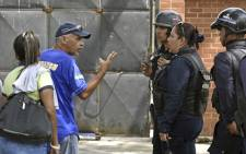 Prisoners' relatives ask for information to police agents guarding police holding cells that caught fire in Valencia, northern Carabobo state, Venezuela, on 29 March 2018. Picture: AFP