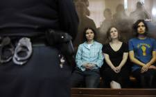 "Members of the all-girl punk band ""Pussy Riot"" Yekaterina Samutsevich (L), Maria Alyokhina (C) and Nadezhda Tolokonnikova (R) sit in a glass-walled cage during a court hearing in Moscow. Picture: AFP."