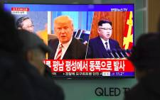 People watch a television news screen showing pictures of US President Donald Trump (C) and North Korean leader Kim Jong-Un (R) at a railway station in Seoul on 29 November 2017. Picture: AFP.