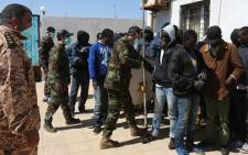 FILE: African migrants wait at a Libyan Naval forces post in Tripoli on 10 April, 2014 after their boat was intercepted en route to Europe and brought back to Libya. Picture: AFP.