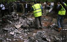 Kenyan forensic experts collect evidence at the site of a police helicopter crash near a charred body on June 10, 2012 in the Ngong hills outside Nairobi. Kenya's Internal Security Minister George Saitoti was killed in the crash. Picture: AFP