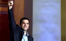 FILE: Syriza leader Alexis Tsipras raises his fist as he greets supporters following victory in the election in Athens. Picture: AFP
