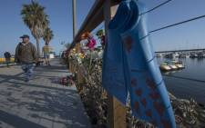 A pair of diving fins and flowers at a memorial wall near the Truth Aquatics moorings where the boat that burned and sank off the Santa Cruz islands early in the morning, was based in Santa Barbara, California on 2 September 2019. Picture: AFP