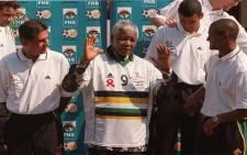 Nelson Mandela wears Shaun Bartlett's numner nine soccer jersey during a photo with the national soccer team in Johannesburg on 5 October, 2000. Source: AFP.
