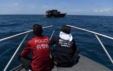 Two boats carrying divers and police officers search an area near Phuket on 7 July 2018, as rescue operations continue for missing tourists following a boat accident on 5 July. Picture: AFP