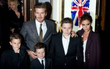 FILE: David and Victoria Beckham pose on the red carpet with three of their children, (L-R) Romeo, Cruz and Brooklyn, as they arrive for the premiere of the Spice Girls musical 'Viva Forever' in central London in December 2012. Picture: AFP.