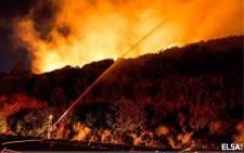 Firefighter battles veld fire on Boyes Drive on 2 March 2015. Picture: Elizabeth Ann Von Hollstein