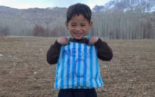 This photograph taken on 24 January, 2016 and provided by the family of Afghan boy and Lionel Messi fan Murtaza Ahmadi, 5, with his plastic bag jersey in Jaghori district of Ghazni province. Picture: AFP.