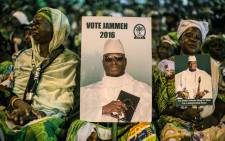 FILE: Supporters of incumbent Gambian President Yahya Jammeh hold a placard reading 'Vote Jammeh' in Banjul on 29 November 2016. Picture: AFP.