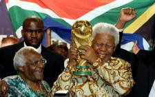 FILE: Nelson Mandela holds the World Cup beside Archbishop Desmond Tutu in Zurich on 15 May 2004. Picture: AFP