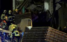 Firefighters inspect a collapsed building, at the Paardenmarkt in Antwerp on 15 January, 2018, after several buildings collapsed following an explosion. Picture: AFP.