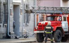A Russian firefighter walks near a fire-engine at building housing the FSB security service in Arkhangelsk on 31 October 2018, after an explosive device went off inside the building. Picture: AFP