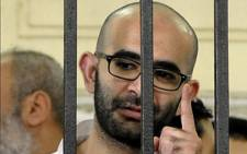 Mahmoud Hassan Ramadan, who has been sentenced to death, looks through the defendant's cage on 19 May, 2014 during his trial and that of others over the deadly violence in the Sidi Gaber neighbourhood of the northern port city of Alexandria on July 5 last year, two days after the army overthrew Egypt's ousted Islamist president Mohamed Morsi. Picture: AFP.