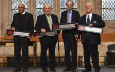 (L-R) South African politician Ahmed Kathrada and South Afrian social campaigner Denis Goldberg, both who were active in the anti-apartheid struggle and formerly imprisoned with Nelson Mandela at Robben Island, along with members of their legal defence team South African-born British lawyer Joel Joffe and Greek lawyer George Bizos, pose holding certificates of their award of the Freedom of the City of London during a ceremony at the Guildhall in London on January 27, 2016. The four along with a third former prisoner Andrew Mlangeni, who was unable to attend, received their awards in reognition of their fight for freedom and recial equality. Picture:  AFP.