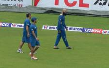 South Africa captain Hashim Amla (right) and Jean-Paul Duminy (centre) walk across the outfield with a team official after a rain shower during the fourth day of the second cricket Test match between Bangladesh and South Africa at the Sher-e-Bangla National Cricket Stadium in Dhaka on 2 August 2015. Picture: AFP.