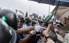 FILE: Police form a line as they make way for an ambulance as pro-democracy protesters shout slogans outside the government headquarters in Hong Kong on 3 October,2014. Picture: AFP.