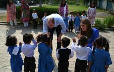 Britain's Prince William (C), Duke of Cambridge, and his wife Catherine (R), Duchess of Cambridge, meet with school children during their visit to a government-run school in Islamabad on 15 October 2019. Picture: AFP
