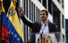 "Venezuela's National Assembly head Juan Guaido waves to the crowd during a mass opposition rally against leader Nicolas Maduro in which he declared himself the country's ""acting president"", on the anniversary of a 1958 uprising that overthrew military dictatorship, in Caracas on 23 January 2019. Picture: AFP"