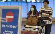 Passengers wear protective masks to protect against the spread of the Coronavirus as they arrive at the Los Angeles International Airport, California, on 22 January 2020. Picture: AFP