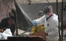 A rescue worker puts a bone fragment into a bag as she collects human remains from a home destroyed by the Camp Fire on 16 November 2018 in Paradise, California. Picture: AFP.