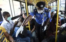 Lagos Commissioner of Police, Hakeem Odumosu (C), speaks to passengers to enforce social distancing in a bus as part of measures to curb the spread of the COVID-19 coronavirus in Lagos, Nigeria on 27 March 2020. Picture: AFP