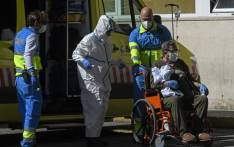 Healthcare workers wearing protective suits push a man on a wheelchair outside the 12 Octubre Hospital in Madrid on 2 April 2020. Picture: AFP