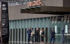 FILE: Journalists (C) wait as armed police officers (R) stand guard outside the Christchurch District Court in Christchurch on 5 April 2019 as alleged gunman Brenton Tarrant, accused of shooting dead 50 Muslims during the 15 March attack on two mosques, appeared for his hearing. Picture: AFP