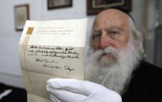 FILE: An Ultra-Orthodox Jewish man displaying one of two notes written by Albert Einstein in 1922. Picture: AFP.