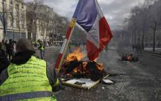 A Yellow Vest protester waves a French national flag while standing behind a burning barricade on the Champs-Elysees in Paris on 16 March 2019, during the 18th consecutive Saturday of demonstrations called by the 'Yellow Vest' (gilets jaunes) movement. Picture: AFP