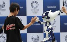 A boy exchanges high-five with Tokyo 2020 robot-type mascot Miraitowa during an unveiling ceremony to mark the one-year to go until Tokyo 2020 Olympic Games at Ajinomoto stadium in Tokyo on 22 July 2019. Picture: AFP