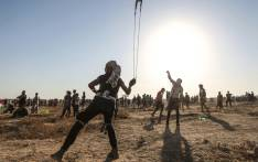 A Palestinian protester uses a slingshot to hurl stones during clashes with Israeli forces near the fence along the border with Israel in the eastern Gaza Strip on 16 August 2019. Picture: AFP