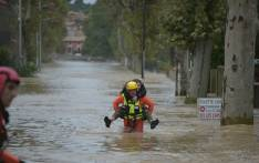 A firefighter helps a youngster in a flooded street during rescue operation following heavy rains that saw rivers bursting banks on 15 October 2018 in Trebes, near Carcassone, southern France. Picture: AFP