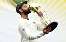 FILE: In this file photo taken on 7 January 2019 India's captain Virat Kohli kisses the Border-Gavaskar trophy as the Indian team celebrates their series win on the fifth day of the fourth and final cricket Test against Australia at the Sydney Cricket Ground in Sydney. Picture: AFP