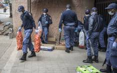 South African police officers confiscate unlawfully sold items at an informal trading post in Hillbrow, Johannesburg, on 28 March 2020 during the second day of the country's lockdown. Picture: AFP
