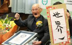 In this Japan Pool picture received via Jiji Press on 12 February 2020, 112-year-old Japanese man Chitetsu Watanabe poses next to calligraphy reading in Japanese 'World Number One' after he was awarded as the world's oldest living male in Joetsu, Niigata prefecture. Picture: AFP
